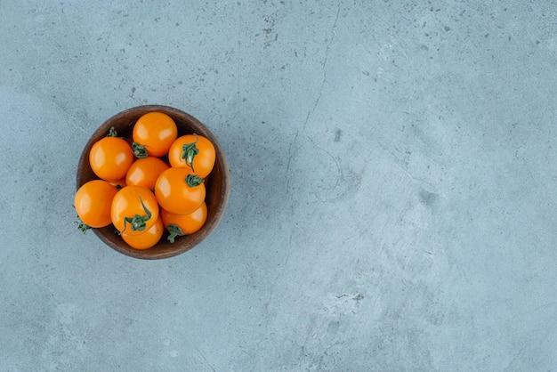 Żółte pomidorki koktajlowe w drewnianej filiżance.