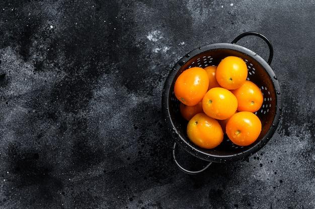 Żółte pomidory czereśniowe w durszlaku. czarne tło. widok z góry. skopiuj miejsce