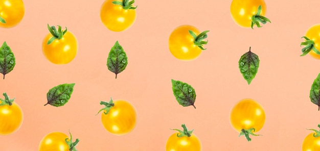 Żółte pomidory i liść bazylowy na białym tle na pomarańczowy widok z góry fruit pattern flat lay