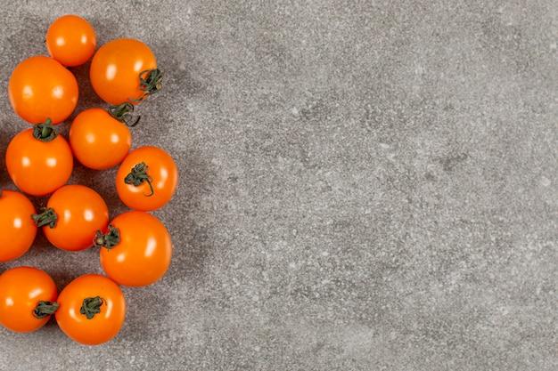 Żółte pomidory koktajlowe na szaro.
