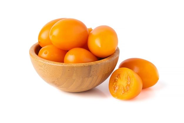 Żółte pomidory w koszu na białym tle