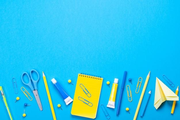 Żółte przybory szkolne na niebieskim tle pastelowych.