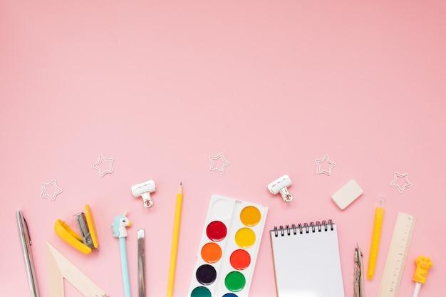 Żółte przybory szkolne na pastelowym różowym tle
