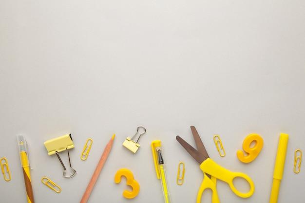 Żółte przybory szkolne na szarym tle. powrót do koncepcji szkoły. widok z góry.