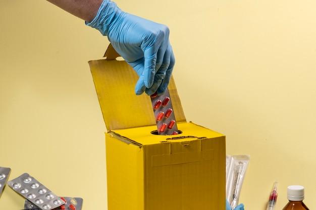 Żółte pudełko na odpady do skażonych lub zakaźnych produktów w szpitalu lub domu. ręczne wkładanie blistra