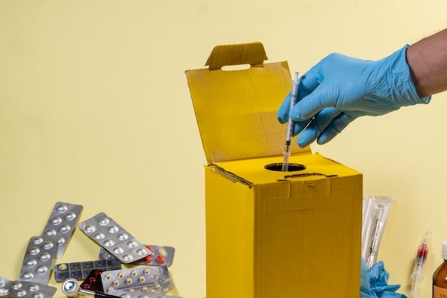 Żółte pudełko na odpady do skażonych lub zakaźnych produktów w szpitalu lub domu. ręczne wkładanie strzykawki