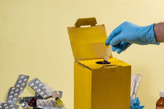 Żółte pudełko na odpady skażone lub zakaźne w szpitalu lub domu. ręczne wkładanie strzykawki