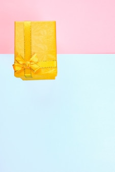 Żółte pudełko z kokardką na różowym i niebieskim tle, urodziny