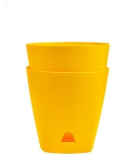 Żółte puste plastikowe doniczki na białym tle