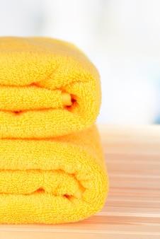 Żółte ręczniki na stole na jasnym tle