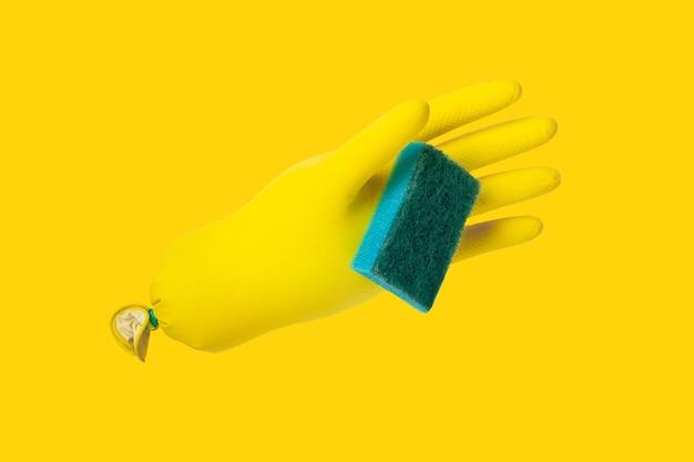 Żółte rękawiczki do czyszczenia trzymające niebieską gąbkę na żółtym tle