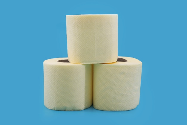 Żółte rolki papieru toaletowego na niebieskim tle.