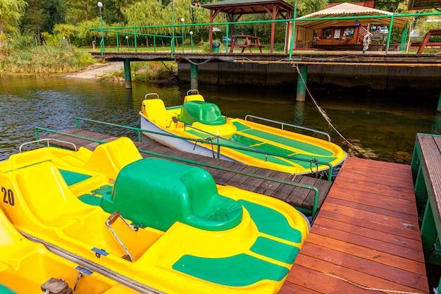 Żółte rowery wodne zablokowane na molo w przystani nad jeziorem w słoneczny letni dzień