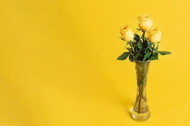 Żółte róże w szklanym wazonie na żółto