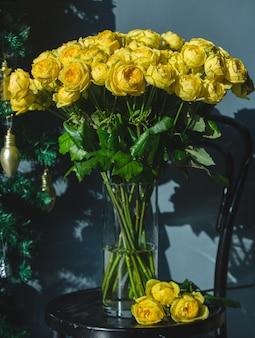 Żółte róże wewnątrz przezroczystego szklanego wazonu z wodą na krześle.