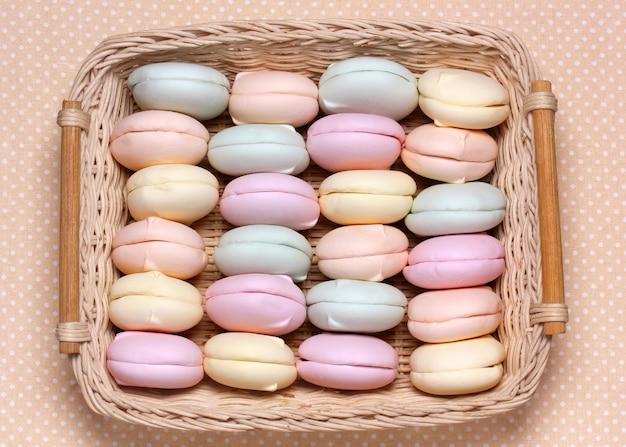 Żółte, różowe i zielone pianki w koszyczku na obrusie w kropki. nieszkliwione kolorowe zefiry, widok z góry. słodki deser owocowy.