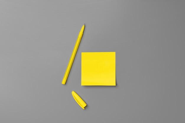 Żółte samoprzylepne notatki i długopis na szarym tle z bliska