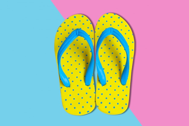 Żółte sandały na różowym i niebieskim tle koloru, płaskie świeckie zdjęcie