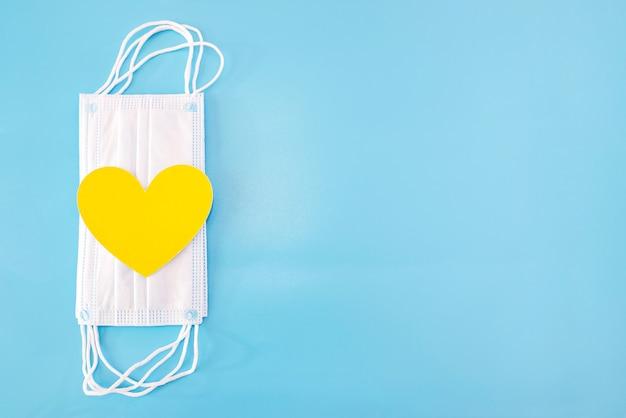 Żółte serce i medyczne maski ochronne na niebiesko. skopiuj miejsce.