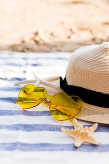 Żółte serce okulary, słomkowy kapelusz i rozgwiazdy na ręcznik plażowy na plaży