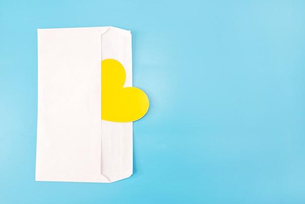 Żółte serce w białej kopercie na białym tle na niebieskim tle. skopiuj miejsce. miejsce na twój tekst.