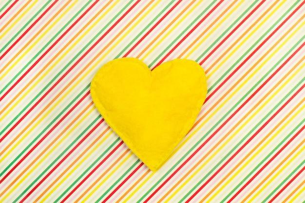 Żółte serce włókienniczych na kolorowym tle w paski