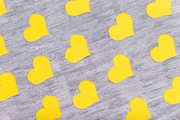 Żółte serduszka na szarym tle, flat lay, modne kolory 2021