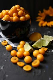 Żółte śliwki z cytryną i limonką na czarnym tle. składniki na dżem. fotografia kulinarna. obraz pionowy. żółty słonecznik, koncepcja jesień, smaczne owoce i witaminy.