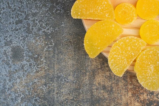 Żółte słodkie galaretki cukierki na drewnianym talerzu