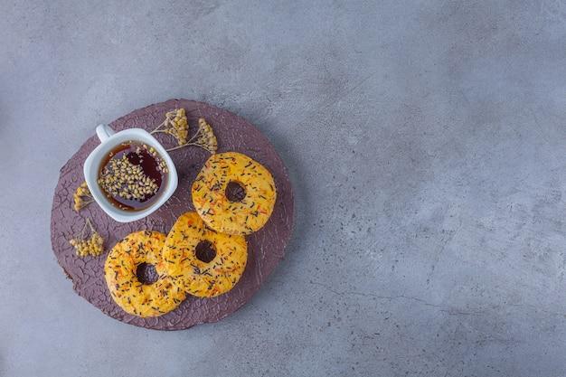 Żółte słodkie pączki i filiżanka herbaty ziołowej na kawałku drewna.