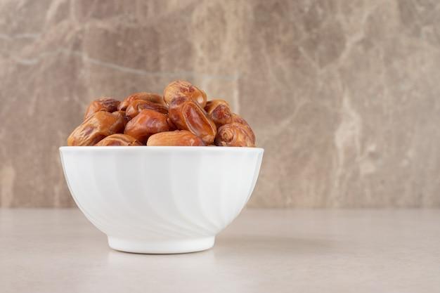Żółte suche daktyle w ceramicznej misce.