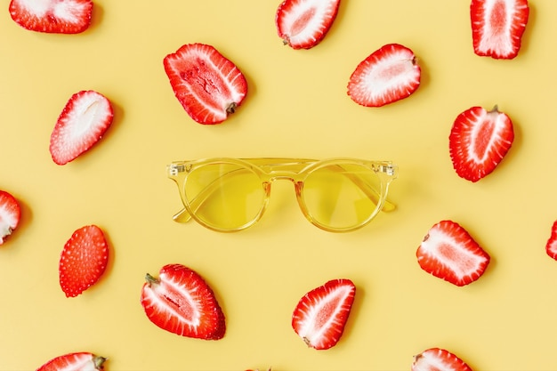 Żółte szklanki na kolorowym tle otoczonym truskawkami.