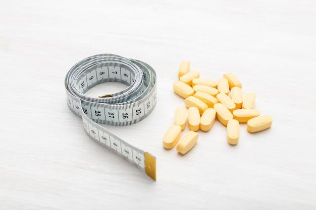 Żółte tabletki odchudzające leżą na białym stole obok miarki. koncepcja odchudzania za pomocą leków.