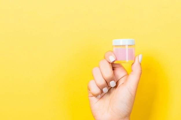 Żółte tło z kobiecej ręki trzymającej słoik kosmetyków