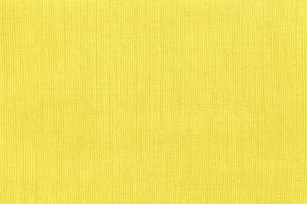 Żółte tło z materiału włókienniczego z wzorem, zbliżenie. struktura tkaniny o naturalnej fakturze.