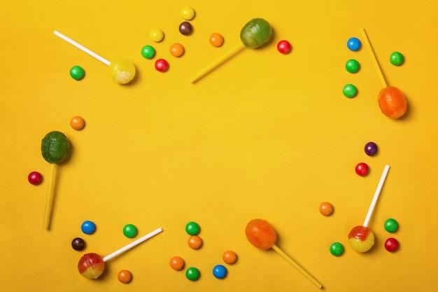Żółte tło z ramką różnych słodyczy