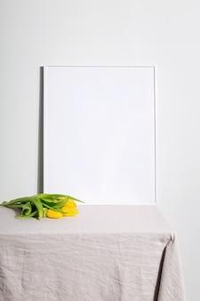 Żółte tulipany i biała ramka na stole z beżowym obrusem. szare tło. skopiuj miejsce