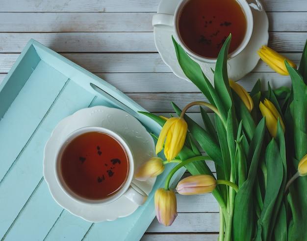 Żółte tulipany i dwie filiżanki czarnej herbaty