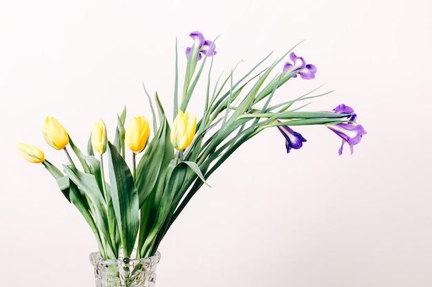 Żółte tulipany i fioletowe irysy w wazonie