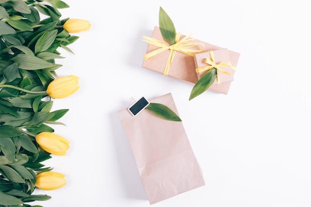 Żółte tulipany i pudełka z prezentami leżą