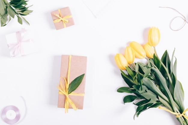 Żółte tulipany i pudełko leżące na białej powierzchni