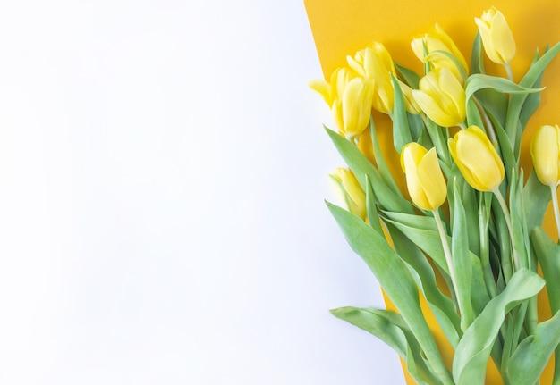 Żółte tulipany kwiaty na żółtym tle. dzień matki, urodziny, walentynki. pojęcie wakacji. symbol wiosny. płaski układanie, widok z góry, kopia przestrzeń