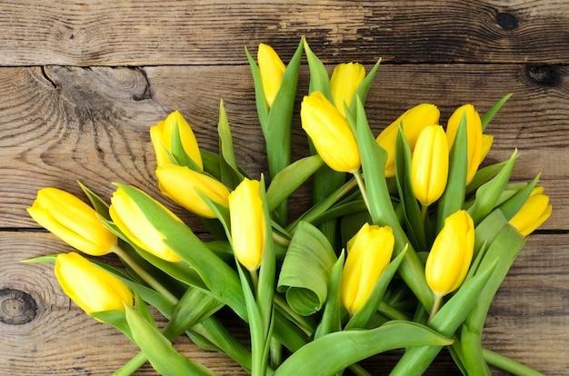 Żółte tulipany leżą na starej drewnianej powierzchni