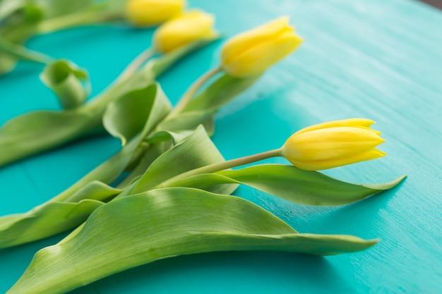 Żółte tulipany leżące na niebieskim drewnianym stole