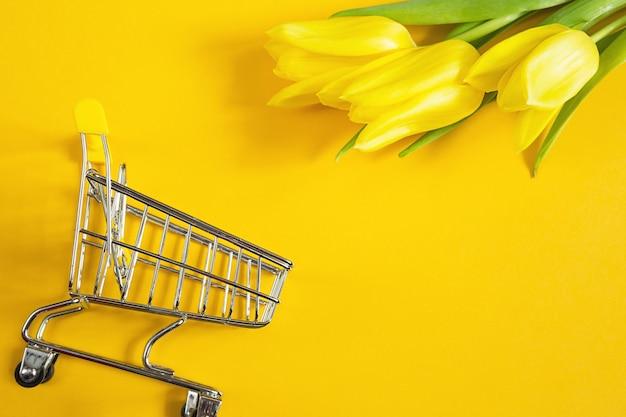 Żółte tulipany na jednolitym kolorowym tle i koszyk.