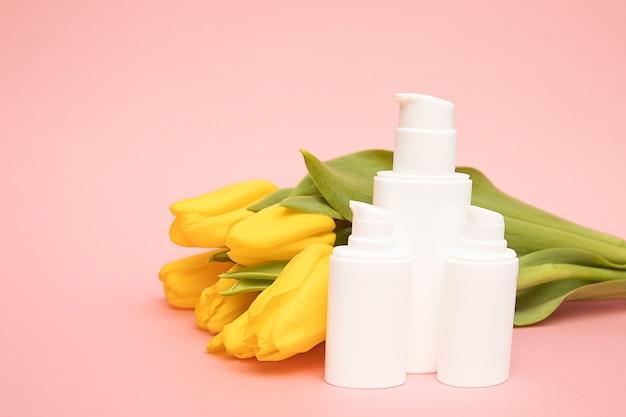 Żółte tulipany na różowym tle z pojemnikami na butelki kosmetyczne. makieta. szczęśliwy dzień matki, koncepcja gratulacje na dzień kobiet, prezent, koreańskie kosmetyki z kwiatami