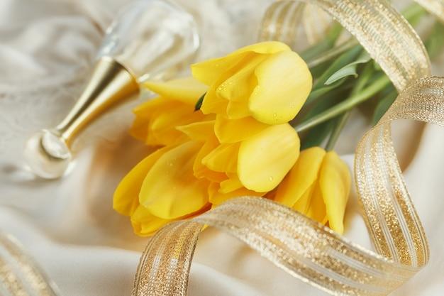 Żółte tulipany, perfumy i złota wstążka na jedwabnym lnie. koncepcja wiosennych wakacji
