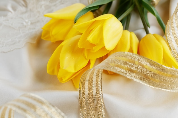 Żółte tulipany, perfumy i złota wstążka na jedwabnym lnie