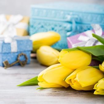 Żółte tulipany w niebieskim metalowym pudełku i pudełkach prezentowych na jasnoszarej powierzchni. kartkę z życzeniami na dzień matki. skopiuj miejsce