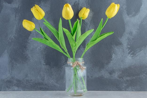 Żółte tulipany w słoiku, na białym stole.